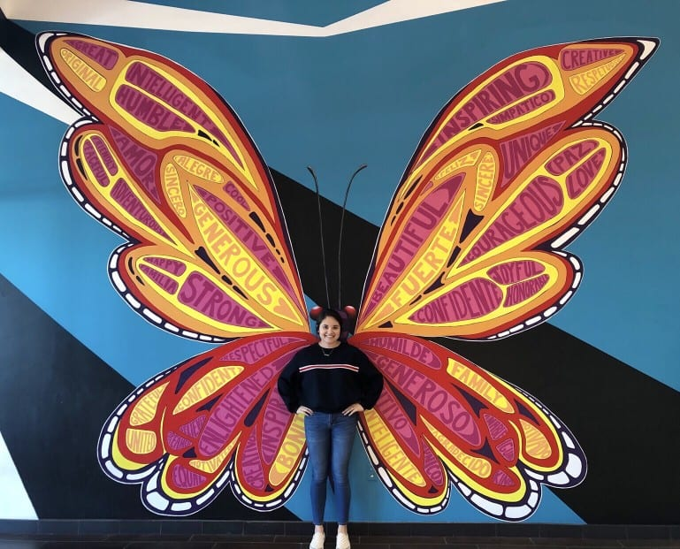 woman standing in front of butterfly wing street art